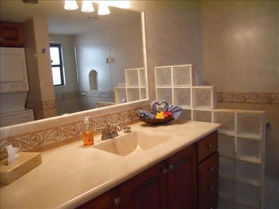 Marble & travertine bath with large glass enclosed shower and washer/dryer