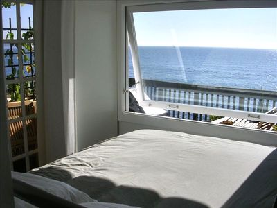 Beach Bungalow: Cozy Bedroom looking out at boats in the day and stars at night.