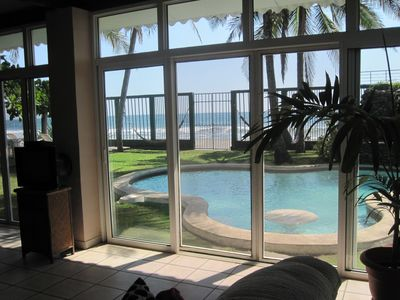 View looking out from living area from sofa area. All glass facing beachfront.