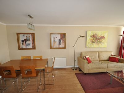 Living room features leather sofa and dining area for 6
