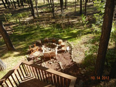 The wooded backyard includes a firepit for your enjoyment