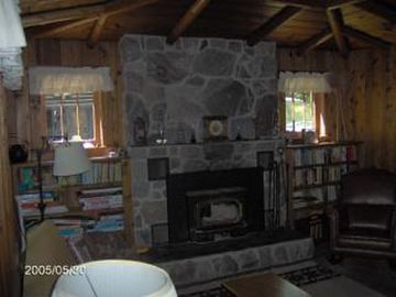 Cozy Wood Burning Stove in Fieldstone Fireplace