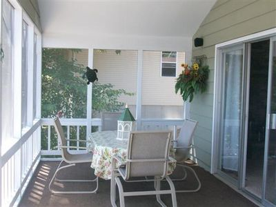 Outdoor dining area on 2nd floor screened in deck
