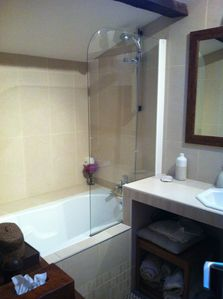 Sandstone bathroom with full length bath and shower