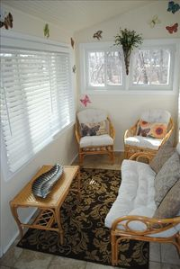 Sunny heated sun room where it's always summer, access to outdoor patio.