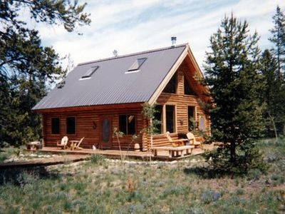 View of cabin on one acre lot with blooming lupine. Note 2 of 4 skylights.