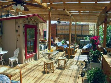 The deck is large. There is a seating area, and a swamp cooler. Ceiling fans too