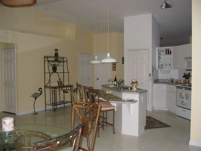 Open kitchen w/breakfast bar & dining area adjacent to the pool entrance