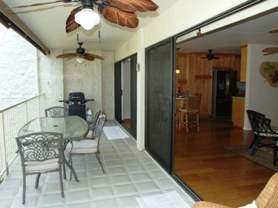 Lanai area with gas barbeque, dining table, chairs for six, chaise lounge, fans.