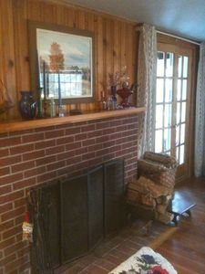 Living room has a fireplace, french doors to screened in porch