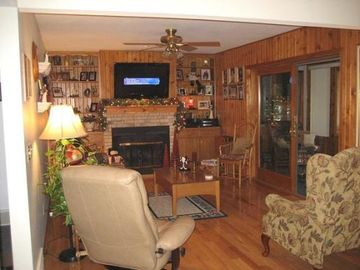 Hardwood floors throughout family room with fireplace and flat screen.