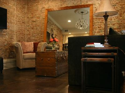 Living room with flat screen TV and original exposed brick walls