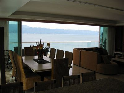 View across the dining area out the fully opened balcony doors.