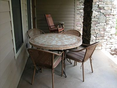 Rocking chairs and outdoor furniture provide seating on the covered porch
