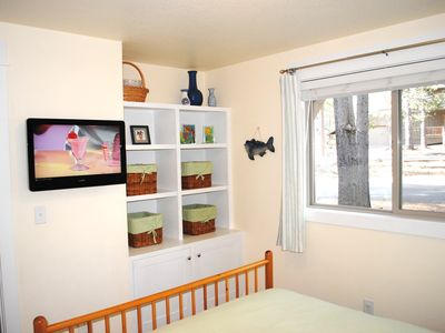View #2 of downstairs Queen room with flat screen tv and built-in storage.