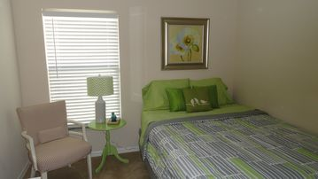 Lovely guest room with queen bed, dresser, & closet.
