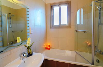 Beautifully fitted bathroom provides a bath tub with over head power shower