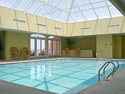 Indoor heated pool with balcony, party area and many lounge chairs