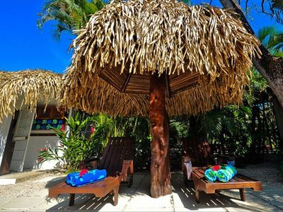 Lounge by the pool in the shade of this Palapa.