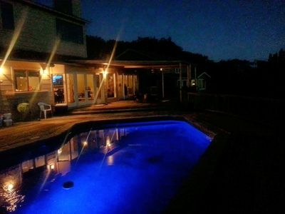 Pool and backyard sparkle at night with multicolored lights and well lit deck