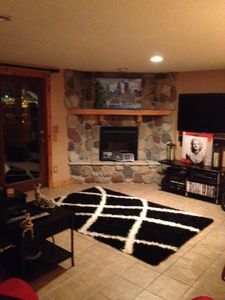 Family room with bar, flat screen, fireplace, and walk out patio on the rive