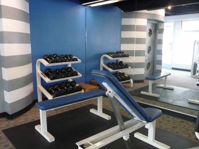 Gym free wights and work out machines overlooking the swimming pool