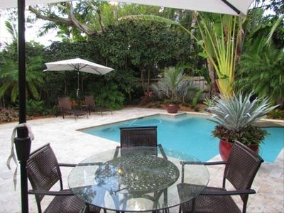 The Pool are is fenced and lushly landscaped with loungers and dining chairs