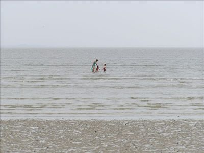 A vast, broad beach at low tide. Mom & kids playing in ankle deep calm water