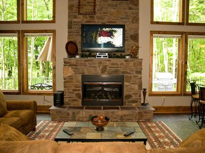 Great Room fireplace overlooking woods and deck that spans entire rear