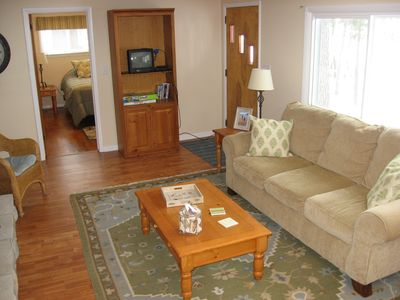 Hillman cottage rental - Living room with two large windows facing lake.
