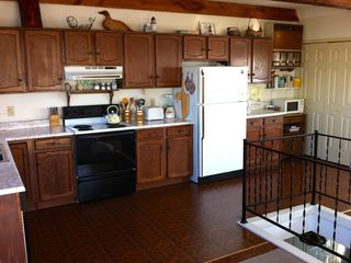 Rye house photo - Open concept kitchen. Notice staircase railing on right side of photo