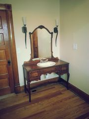 Colorado Springs house photo - Antique vanity matches the bed in this charming first floor master bedroom.