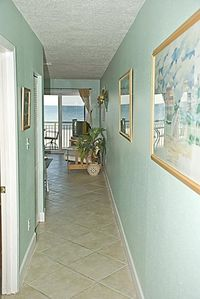 ENTRY HALL AND PARTIAL VIEW OF LIVING AREA, BALCONY, AND GULF OF MEXICO