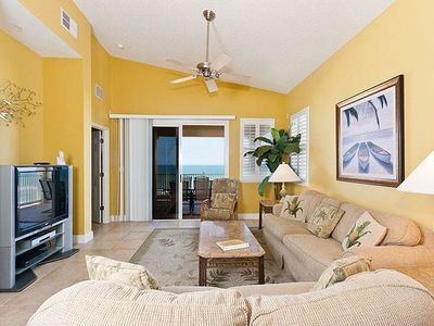 Living room has beautiful views of the ocean - An open floor plan and bright, tropical-themed accents welcome you to 665 Cinnamon Beach. Sit in comfort and enjoy the ocean front views outside or stay in watch the HDTV!