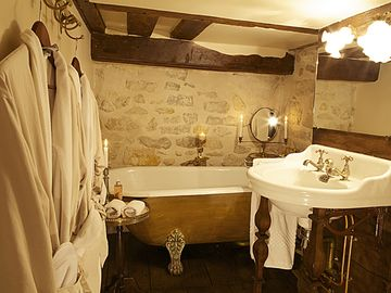 A luxurious soaking tub, sink & toilet in the loft; luxury hotel robes/slippers