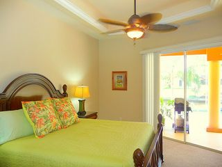 Cape Coral house photo - Master bedroom with cooling tropical ceiling fan and open to pool and lanai