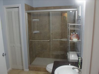 Remodeled bathroom with full size shower, new sink, and toilet.