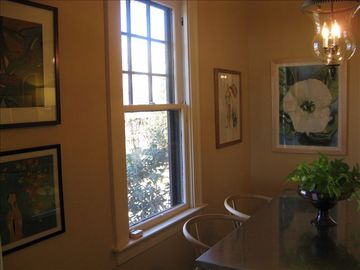 There is a window in the dining room with nice art.