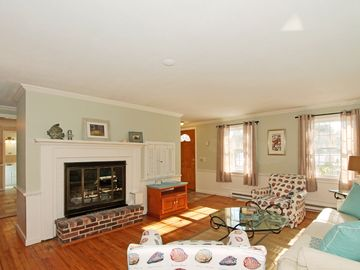 Living room with fireplace and hardwood floors open to adjacent dining room.