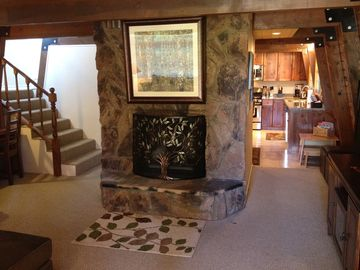 Vaulted wood beamed ceilings and beautiful stone fireplace in den.