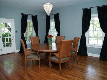 Dining room with crystal chandelier, oak floors, silk curtains