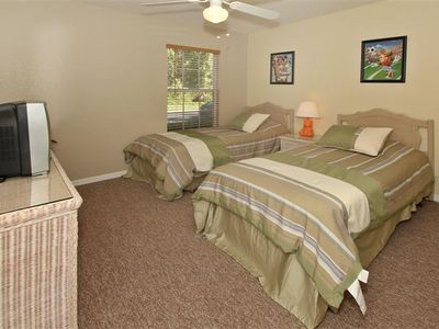 Bedroom Five with twin beds, ceiling fan and TV.