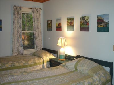 Twin bedroom with woods view; window with water view not shown