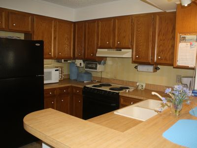 Kitchen with fullsize fridge, stove, dish washer, microwave, pots, pans, etc.