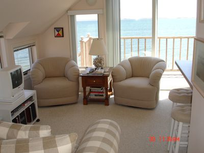 Living room has a love seat, two swivel chairs, and sit-down harbor views