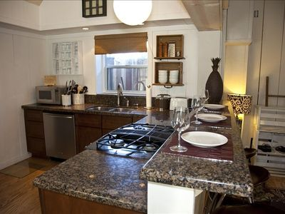 Spacious gourmet kitchen with granite countertops, jenn-air downdraft stove