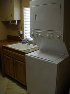 Laundy room attached to kitchen with washer/drier and deep sink
