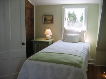 Third bedroom has two twin beds, harbor and village views and a writing desk.
