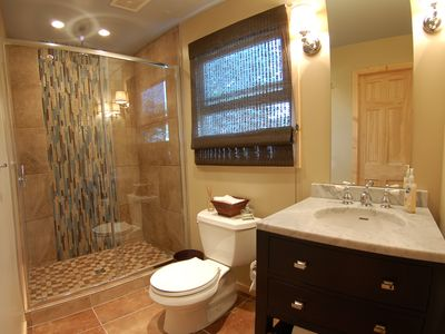 Newly renovated bathroom with rainfall shower, carrera marble and porcelain tile