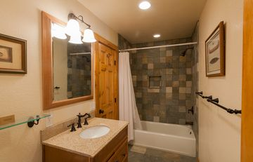 Spa-like bathroom w/ stone tile, granite counter and 2 entrances (master / hall)
